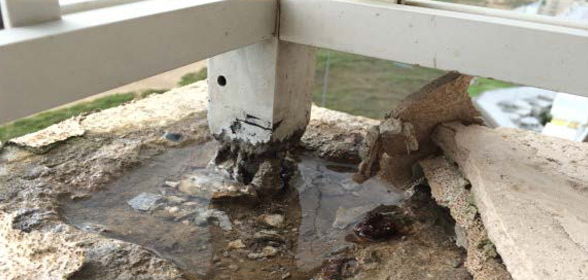 Photo of galvanic corrosion rotting a railing post.