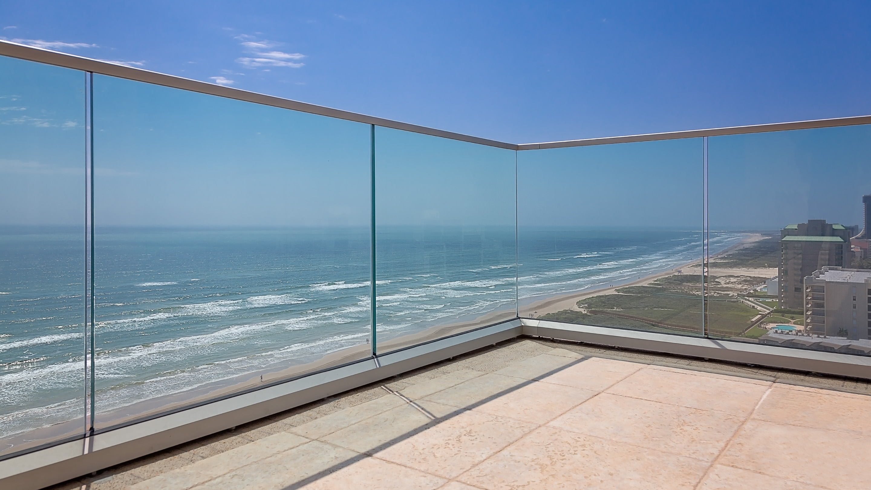 Isola Bella is a condominium in South Padre Island which features custom glass railing by Poma.